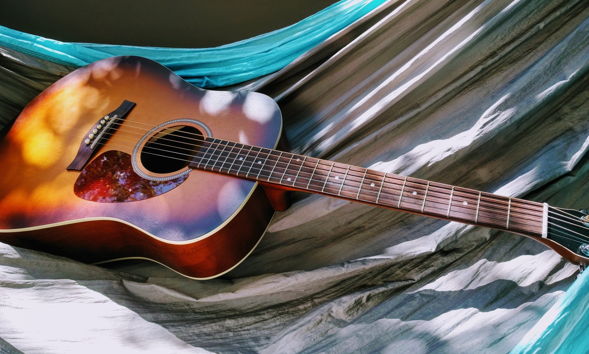 Image of a guitar laying on a blanket